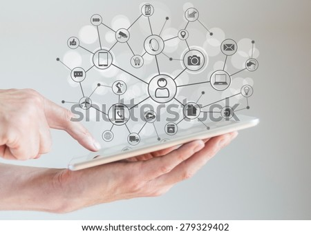 Internet of Things concept (IoT) with male hands holding tablet or large smart phone in order to connect various devices and smart machines.