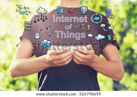 Internet of Things concept with young man holding his smartphone outside in the park toward sunset