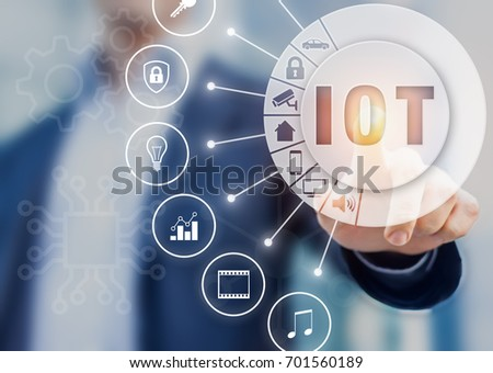 Internet of Things technology with connected objects, hand touching button with text IOT on AR (Augmented Reality) interface with icons #701560189
