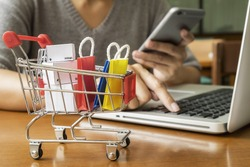 Internet online shopping concept with smartphone and shopping-cart.Vintage tone retro filter effect,soft focus(selective focus)