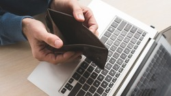 Internet scam. Fraud danger online. Man holding an empty wallet because he lost his money to a fraudster