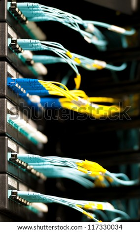 Internet service provider equipment. Focus on panel with optic cables connected to panel in datacenter. Network server room. Modern technology. Yellow and blue cables contrast with dark background.