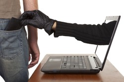 Internet theft - a gloved hand reaching through a laptop screen to steal a wallet from a man.