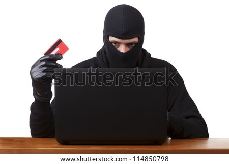 Internet Theft - a man wearing a balaclava and holding a credit card while sat behind a laptop, white background.
