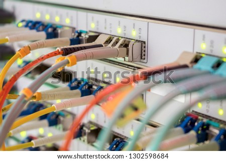 Internet wires are connected to the central router interfaces. There are many optical patchcards in the data center server room. Telecommunications cables are connected to the main server. #1302598684