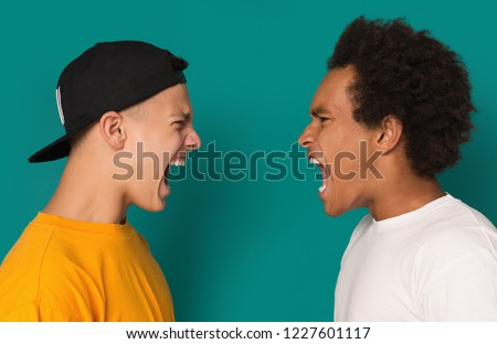 Interpersonal conflict. Two angry teens yelling, shouting at each other blaming for problems on blue background. #1227601117