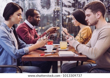 Interpersonal distance. Nice melancholic four friends staring at phones while gathering at cafe and keeping silence