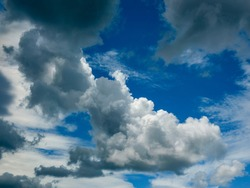 Interplay of sunlight and shadow among irregular cumulus clouds crossing partly blue sky on a summer afternoon in west central Florida
