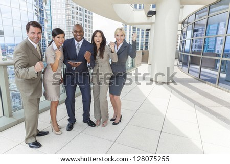 Interracial business team, men & women, businessmen & businesswomen, using tablet computer and celebrating success on a city rooftop