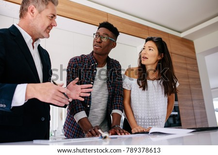 Interracial couple having consultation with a real estate agent inside a new home. Mature male realtor discussing the contract with customer.
