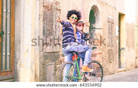 Interracial couple of tourists on bike tour turning pointing finger at old city alley view - Happy traveler friends riding bicycle looking around ancient european streets - Alternative tourism concept #643556902
