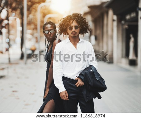 Interracial couple on the city street: a young charming African girl with braids, in a black dress and an asian guy with curly hair, in sunglasses holding a jacket of his suit; sunny autumn day