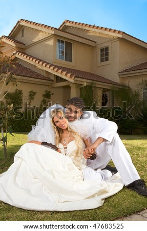 Interracial couple outdoors. Smiling laughing newlywed young Caucasian woman and mid aged ethnic black man of African American and Italian ethnicity sitting on lawn in front yard
