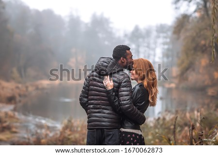 Interracial couple posing in autumn leaves background, black man and white redhead woman