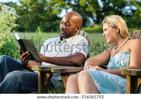 Interracial couple reading a book at the park on a sunny summer afternoon