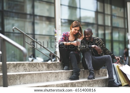 Interracial couple resting after shopping