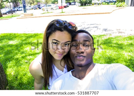Interracial couple sitting on grass outside under a shady tree, on a sunny day