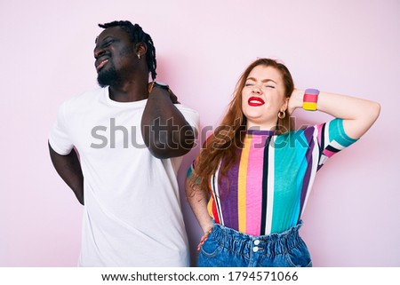 Interracial couple wearing casual clothes suffering of neck ache injury, touching neck with hand, muscular pain  ストックフォト ©