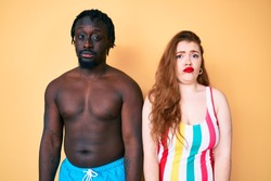 Interracial couple wearing swimwear depressed and worry for distress, crying angry and afraid. sad expression.