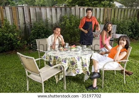 Interracial family having back yard barbecue