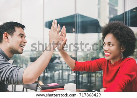Interracial friends, Asian man and a black woman, making high five celebrating after a business meeting at a coffee shop cafe