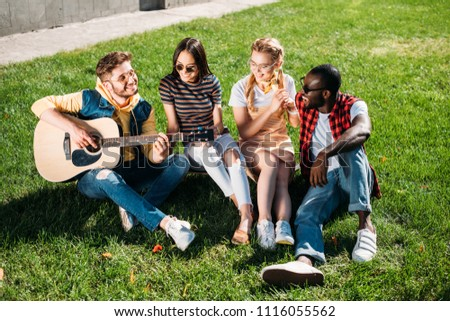 interracial group of friends with acoustic guitar resting on green grass in park on summer day #1116055562