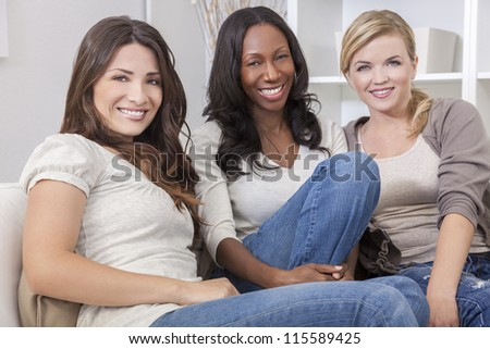 Interracial group of three beautiful young women friends at home sitting together on a sofa smiling and having fun
