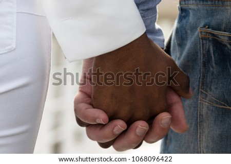 Interracial love. Man and woman of black race shaking hands
