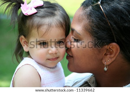 Interracial mother and daughter playing in their yard