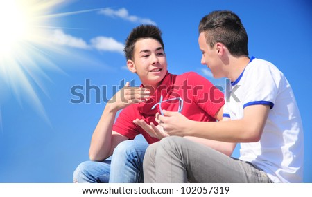 Interracial teenage boys talking outdoor; asian and caucasian