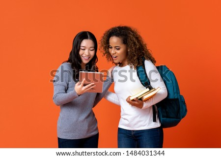 Interracial university students as friends looking at tablet computer isolated on colurful orange background