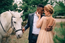 Interracial wedding. African man and Caucasian woman stand embracing near a white horse.