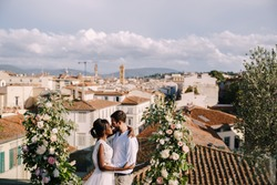 Interracial wedding couple. A wedding ceremony on the roof of the building, with cityscape views of the city and the Cathedral of Santa Maria Del Fiore. Destination fine-art wedding in Florence, Italy