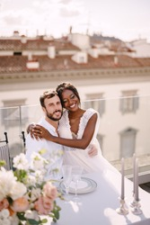Interracial wedding couple. Destination fine-art wedding in Florence, Italy. African-American bride and Caucasian groom are sitting at the rooftop wedding dinner table overlooking the city.