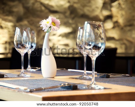 Interrior of restaurant with served table and stone wall