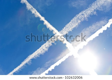 intersection of three chemtrails under the sun - stock photo