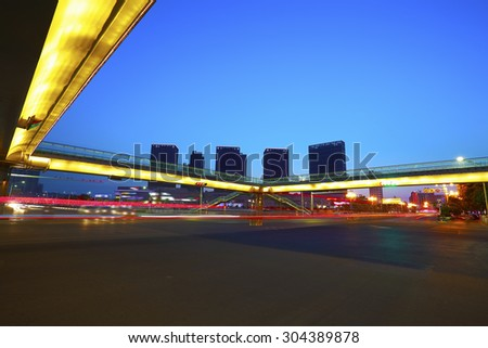 Intersection of urban footbridge and highway auto with light trails of night scene