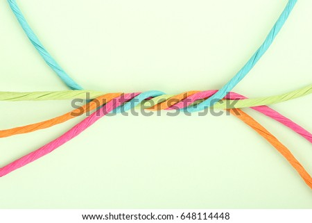 intertwined colorful cords on paper, abstract unity concept #648114448