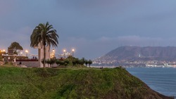 Intihuatana park with panoramic view of Miraflores district and Morro Solar hill on a background day to night view, in Lima, Peru. Palm and caffee with illuminated street lights