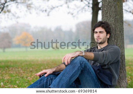 Intimate portrait of man outside in a park.