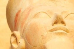 Intimate portrait of pharaoh Osirus shows remnants of color across the ancient cracked face at the Temple of Hatshepsut in West Bank, Luxor, Egypt