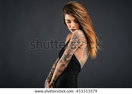Intimate woman studio portrait with long black dress and tattoos against dark background.