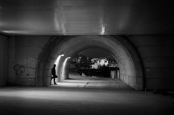 Intimidating man in a tunnel under a bridge at night.