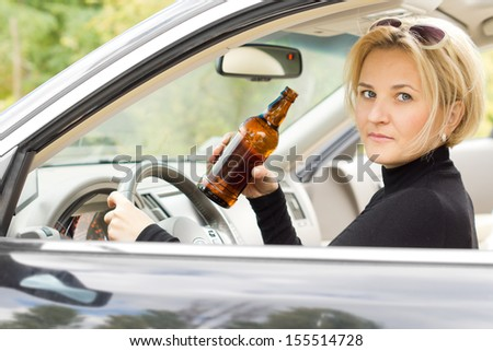 Intoxicated woman driver looking out of her side window with a serious expression as she drives by holding a bottle of booze in her hand