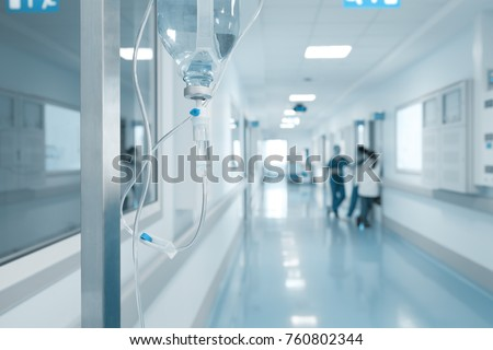 Intravenous drip on the rack on the background of talking nurses in the hospital corridor. #760802344