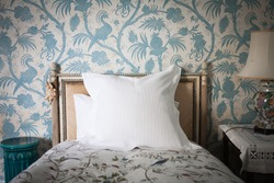 Intricate wooden headboard single bed against blue and white antique bird wall paper