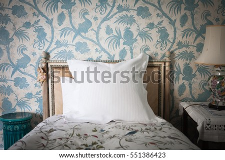 Intricate wooden headboard single bed against blue and white antique bird wall paper #551386423