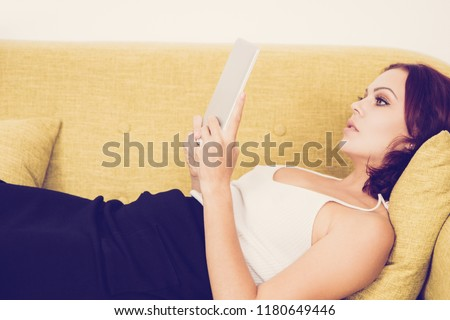 Introspective business lady viewing email on device while lying on sofa. Serious pensive young woman focusing on work in rest room. Technology concept