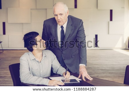 Introspective colleagues elaborating business plan while discussing papers. Inquisitive intern asking business mentor about documents. Brainstorming concept