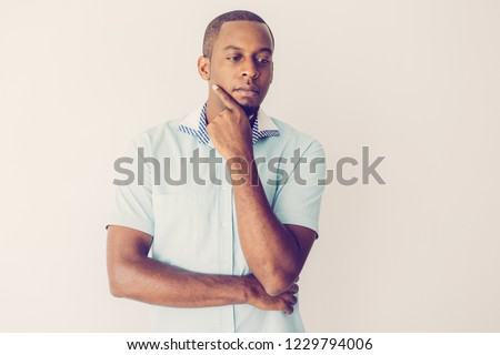 Introspective handsome young African man rubbing chin and looking down. Pensive guy thinking alone. Contemplation concept
